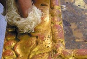 The surface of the frame is then tamped with cotton waste to help dry the remaining wash. The effects of wiping off the wash can be seen by the amount of gold that has been removed by this point.